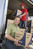 Man unloading truck of cardboard boxes — Stock Photo