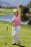 Woman gesturing on golf course — Stok fotoğraf