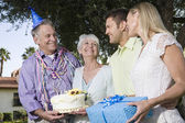 Couples with birthday gift and cake — Stock Photo