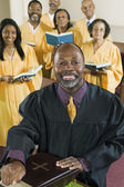 Minister with Bible amd gospel choir — Stock Photo