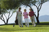 Women walking on golf course — Stock Photo
