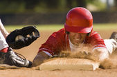 Baseball player sliding into base — Stock Photo