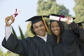 Two graduates hoisting diplomas — Stock Photo