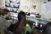 People eating at sushi bar — Stock Photo