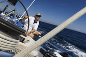Sailor at helm of yacht on ocean — Stock Photo