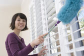 Woman dusting window — Stock Photo