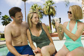 Woman video taping couple by pool — Stock Photo