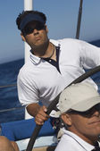 Man at Helm of Sailboat on ocean — Stock Photo