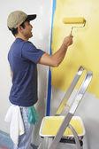 在墙上涂上黄色油漆的男人 — 图库照片