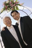 Groom with father under archway — Stock Photo