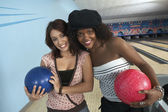 Friends with balls in bowling alley — Stock Photo