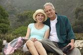 Couple with binoculars in countryside — Stock Photo