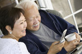 Senior couple using mobile phone — Stock Photo