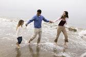 Family walking through surf — Stock Photo