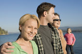 Family standing on lake shore — Stock Photo