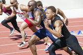 Male athletics sprinting on running track — Stock Photo