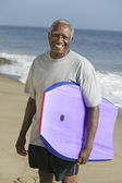 Senior man holding surfboard — 图库照片