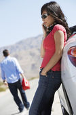 Woman on call by car while man with gasoline can — Stock Photo