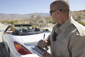 Police officer writing traffic ticket — Stock Photo