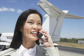 Businesswoman with airplane in background — Stock Photo