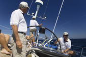 Sailors at helm of sailboat — Stock Photo
