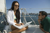 Man with woman using laptop on sailboat — Foto de Stock