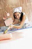 Vrouw toepassing van verf op een muur — Stockfoto