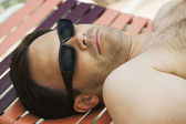 Man lying on sunlounger. — Stock Photo