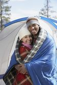 Couple wrapped in blankets at the campsite — Stock Photo