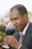 Elegant man tasting red wine — Stock Photo