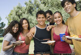 People gathered around grill at outdoor picnic. — Stock Photo