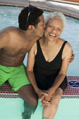 Man kissing mother at swimming pool — Stock Photo
