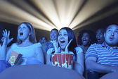 People watching horror movie in the theatre — Stock Photo