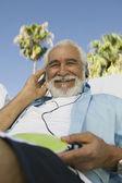 Senior Man listening to headphones — Stock Photo