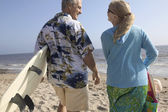 Couple at beach with surfboards — ストック写真