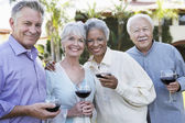 Couples standing outside with wine glasses — Stock Photo