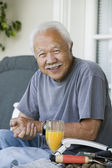 Senior man with orange juice — Stock Photo