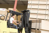 Male laborer with forklift stacking wood — Stock Photo