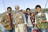 Man with three sons holding fishing rods — Stock Photo