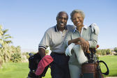 Senior couple in golf course smiling — Stock Photo