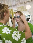 Adam kız arkadaşına güneş gözlüğü koyarak — Stok fotoğraf