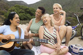 Women singing with guitar player — Stock Photo