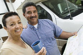 Mid-adult couple standing beside caravan — Stock Photo