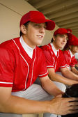Baseball team-mates sitting in dugout — Стоковое фото