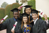 Graduates hoisting diplomas — Stock Photo