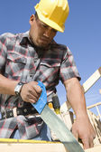 Construction worker sawing — Stock Photo
