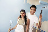 Couple standing against partially painted wall — Stock Photo
