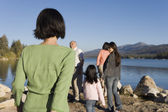 Family walking by lake — Stock Photo