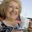 Stock Photo: Senior Womlistening to music player