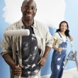 Couple holding paint rollers — Stock Photo
